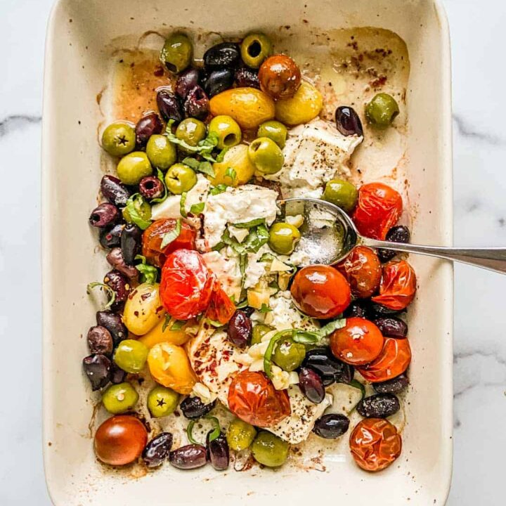 An overhead shot of a baking dish with feta, olives, and tomatoes.