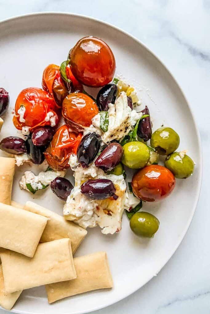 A plate with baked feta, olives, and tomatoes served alongside crackers.