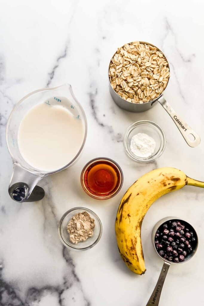 A measuring cup of almond milk, a cup of oats, a banana, a third cup of blueberries, a bowl of baking powder, a bowl of maple syrup, and a bowl of chai spice.