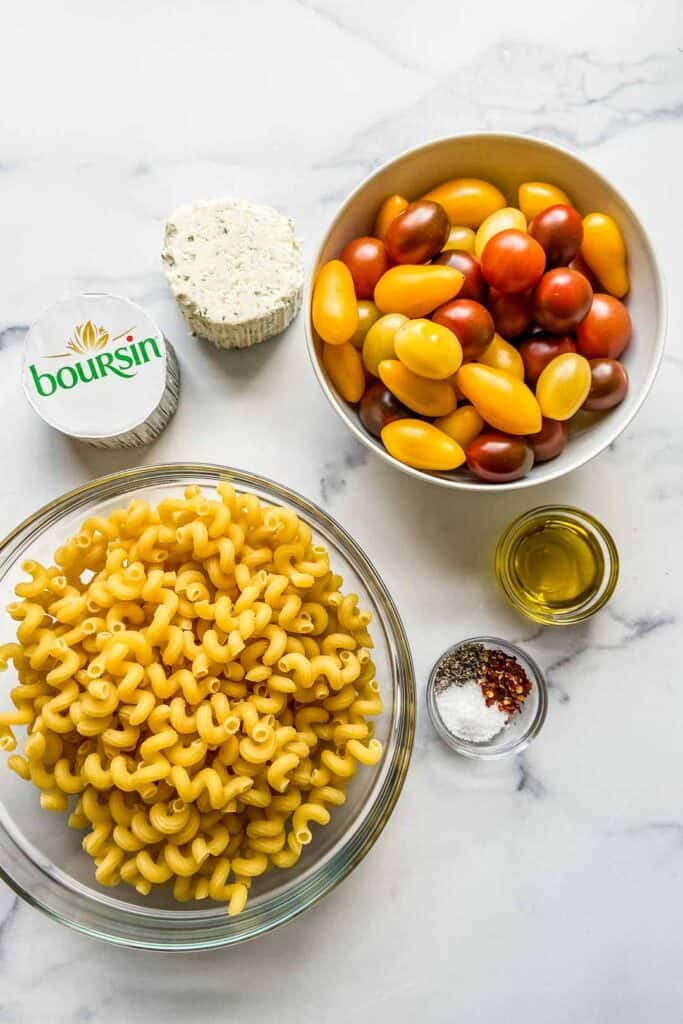 A bowl of pasta, a bowl of cherry tomatoes, two blocks of Boursin cheese, a bowl of olive oil, and a bowl of spices.
