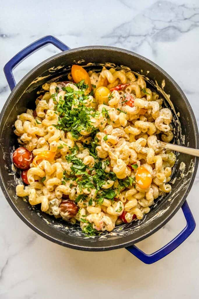 A blue dutch oven with pasta topped with herbs.
