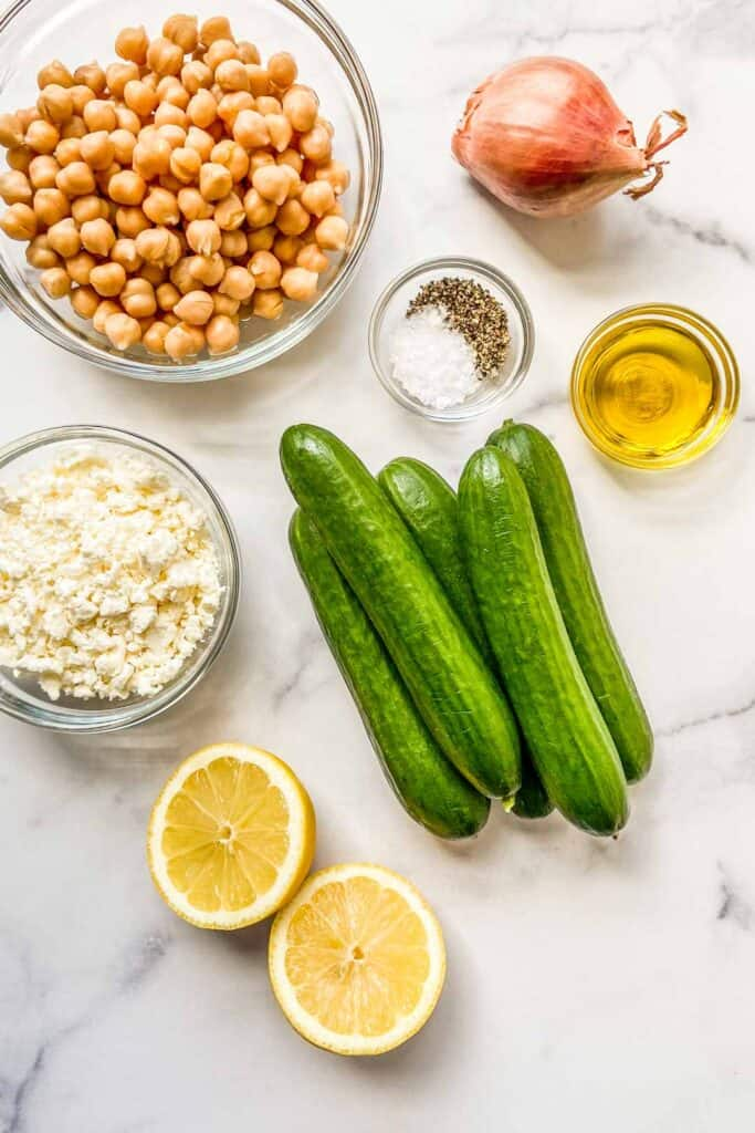 A bowl of chickpeas, several small cucumbers, a bowl of feta, a halved lemon, a bowl of olive oil, a shallot, and a bowl of salt and pepper.