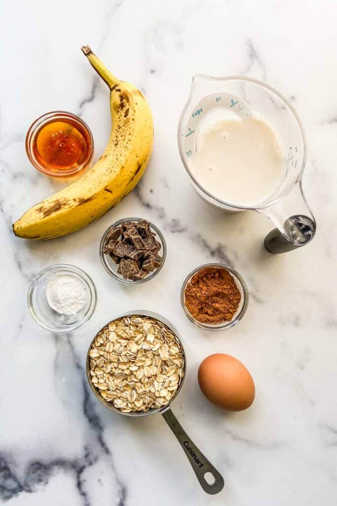 A banana, measuring cup of almond milk, bowl of honey, bowl of chocolate chunks, bowl of baking powder, bowl of cocoa powder, measuring cup of oats, and an egg sitting on a marble background.