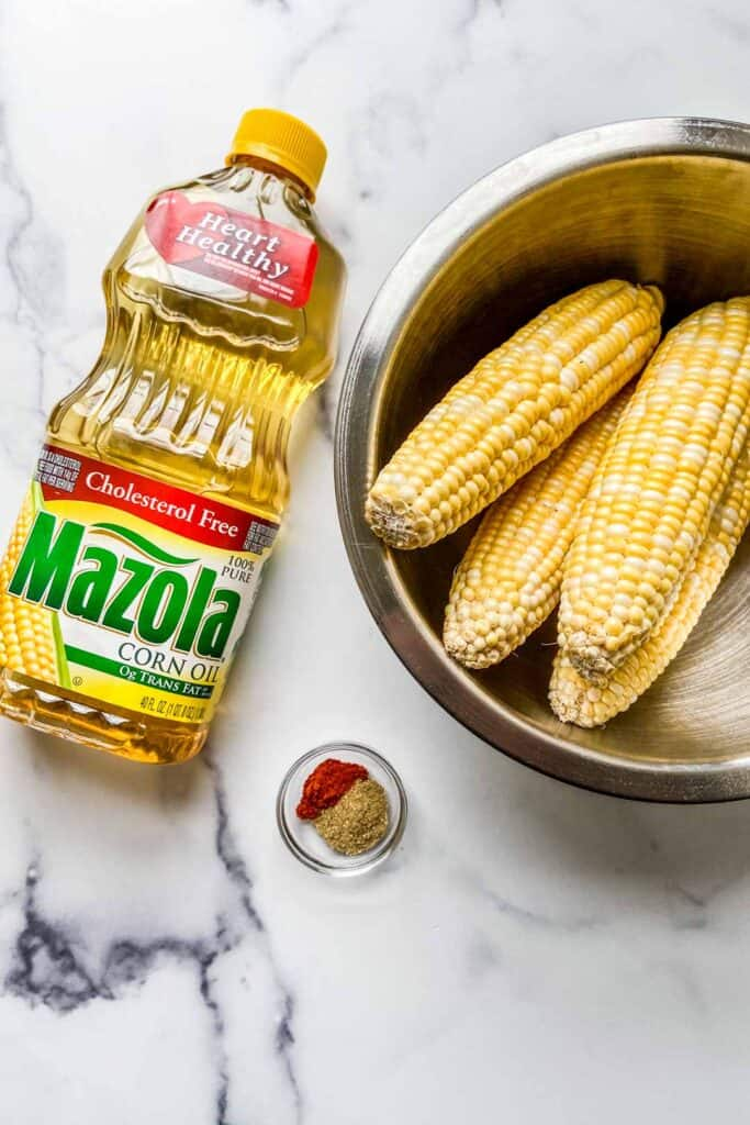 A bottle of Mazola corn oil, a large bowl with 4 ears of corn, and a small bowl with spices.