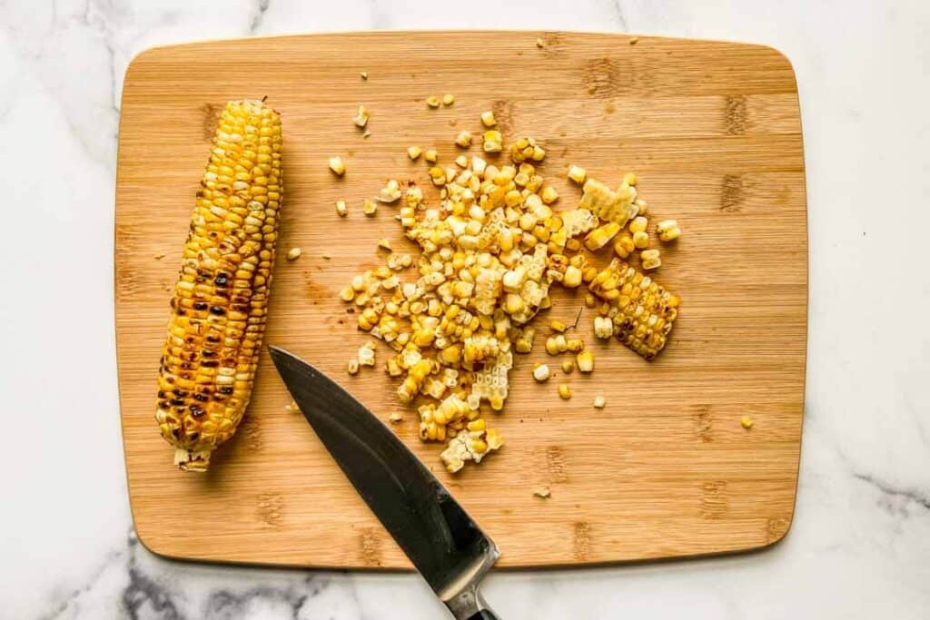 A cutting board with an ear of corn, a knife, and a pile of corn.