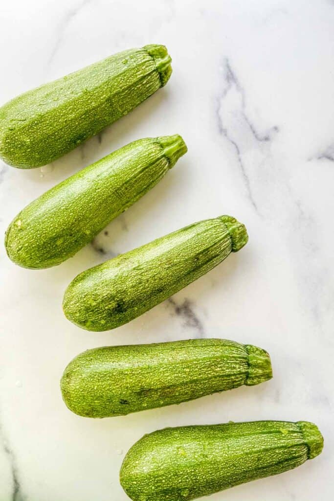 Several small marrow squash on a marble background.