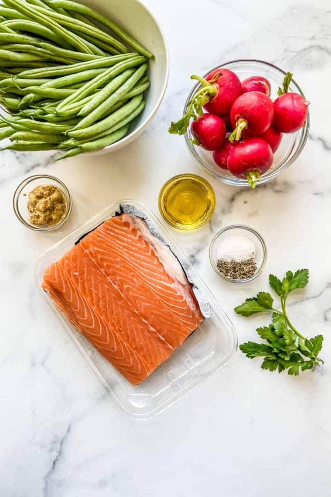 A salmon fillet, green beans, radishes, salt and pepper, mustard, and olive oil on marble background.