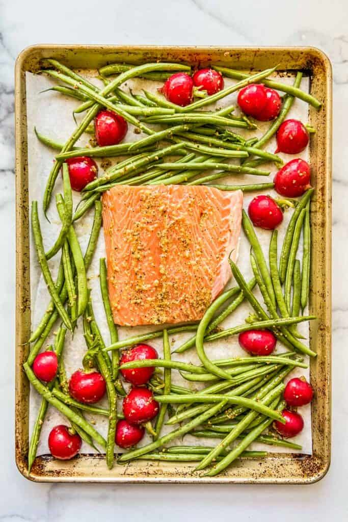 A sheet pan with an uncooked piece of salmon, green beans, and radishes.