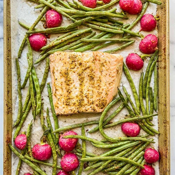 Salmon, green beans, and radishes on a sheet pan.