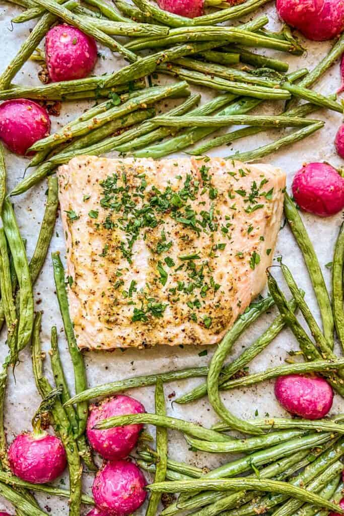 A closeup shot of a cooked salmon fillet surrounded by green beans and radishes.