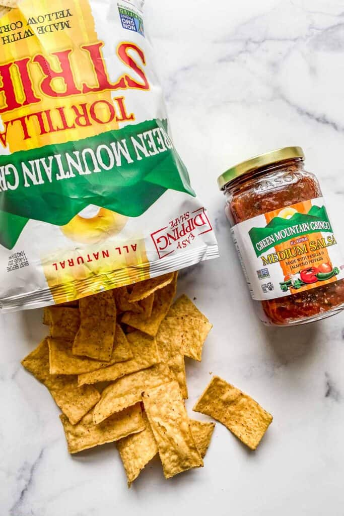 An open bag of tortilla strips and a can of salsa.