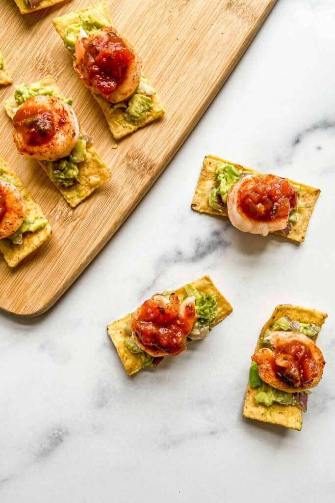 Grilled shrimp bites on a marble background and a bamboo cutting board.