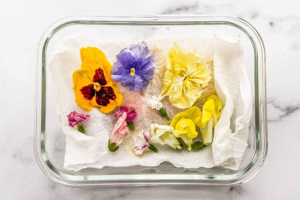 Edible flowers on a paper towel in a glass container.