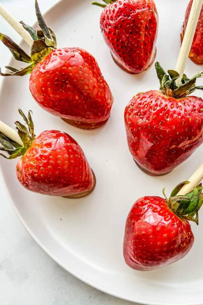 A closeup shot of tanghulu strawberries on a white plate.