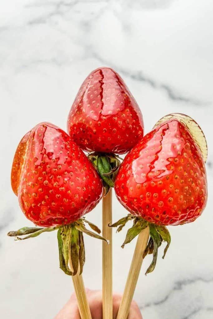 Three candied strawberries on wooden skewers.