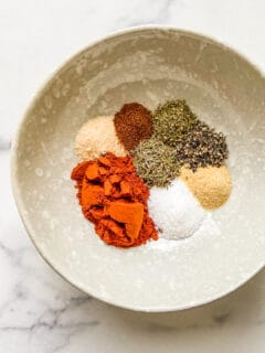 Spices for blackening seasoning in an off-white bowl.