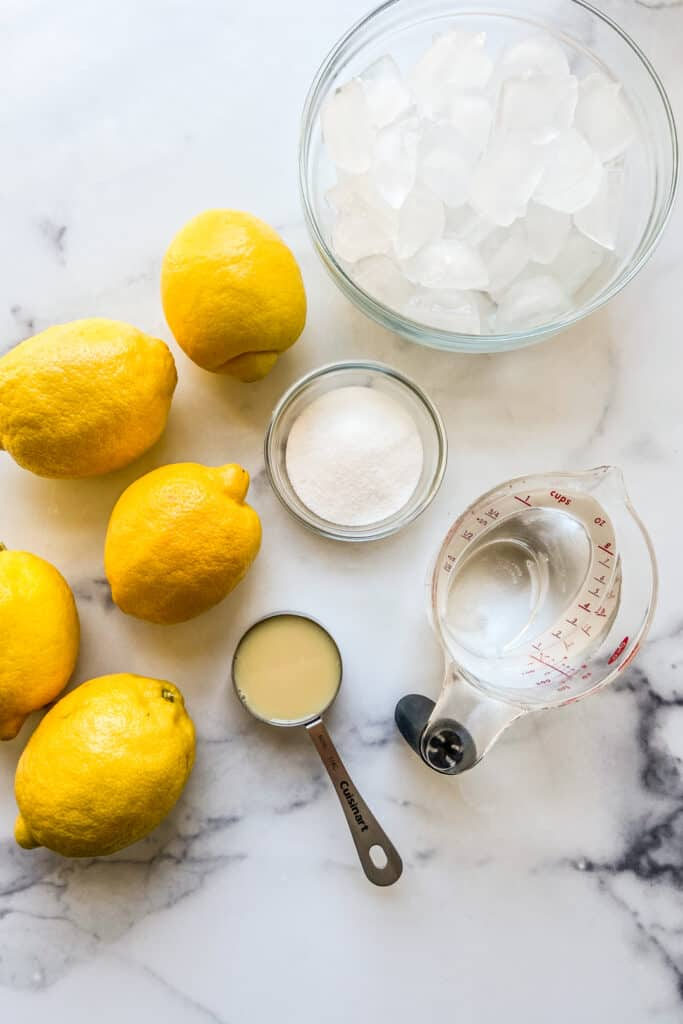 Five lemons, a bowl of ice, a bowl of sugar, a measuring cup of sweetened condensed milk, and a measuring cup of water.