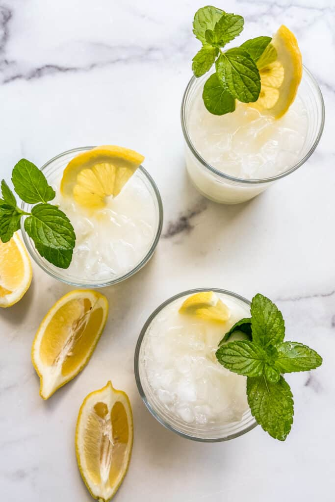 Three glasses of creamy lemonade topped with mint and sliced lemons.