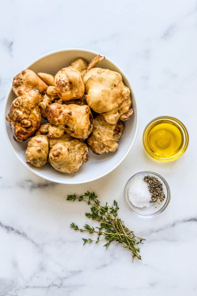 A bowl of sunchokes, a bowl of olive oil, a bowl with salt and pepper, and some fresh thyme.