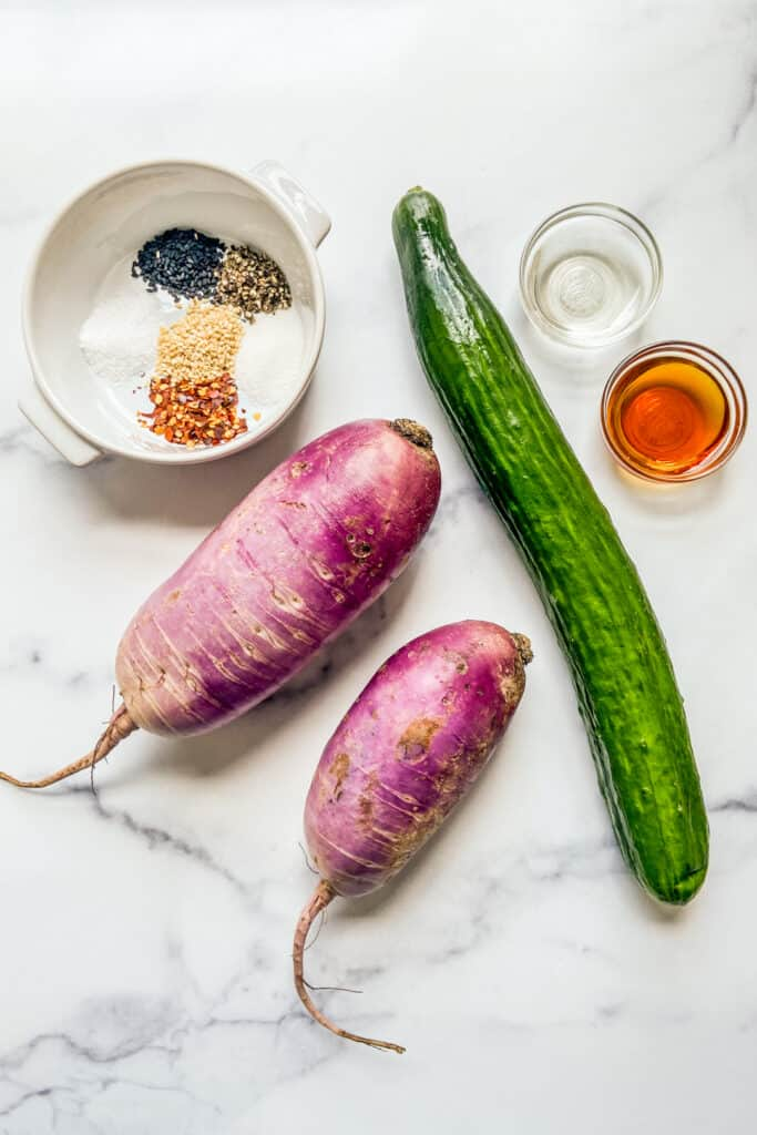 An English cucumber, two purple daikon radishes, a bowl of sesame oil, a bowl of rice wine vinegar, and a ramekin with sesame seeds and spices.