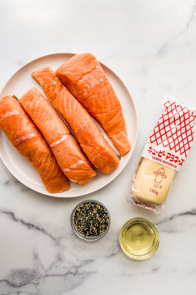 A plate of salmon fillets, a small bottle of kewpie mayo, a small bowl of furikake seasoning, and a small bowl of canola oil.