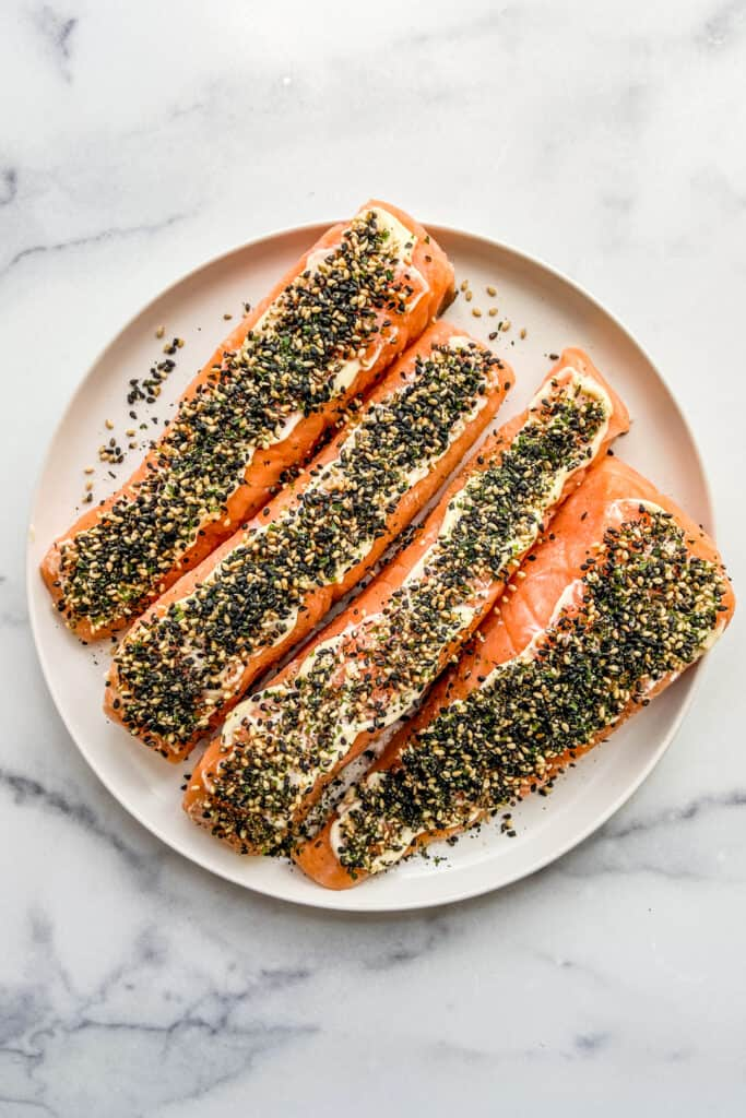 Uncooked salmon fillets with mayo and furikake on top.