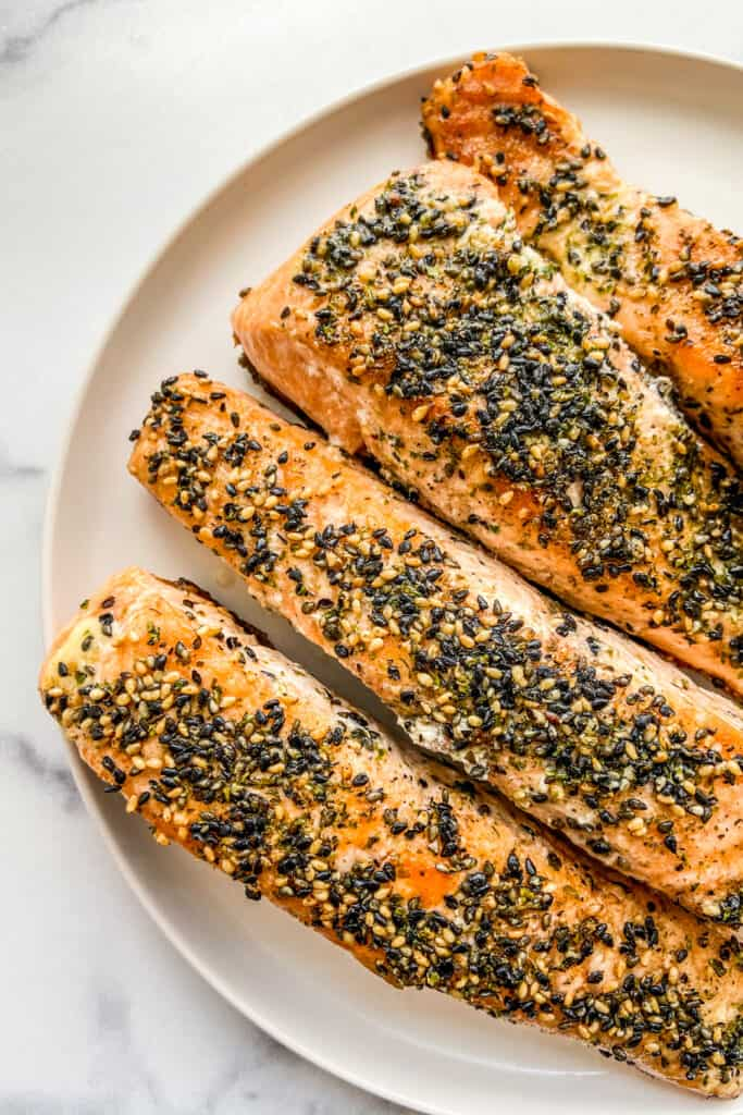 Four cooked salmon fillets topped with furikake seasoning on a white plate.