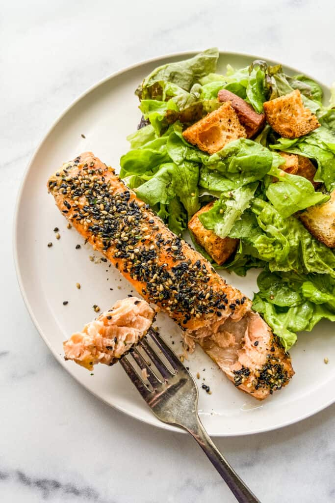 A salmon fillet topped with furikake next to a green salad on a white plate.