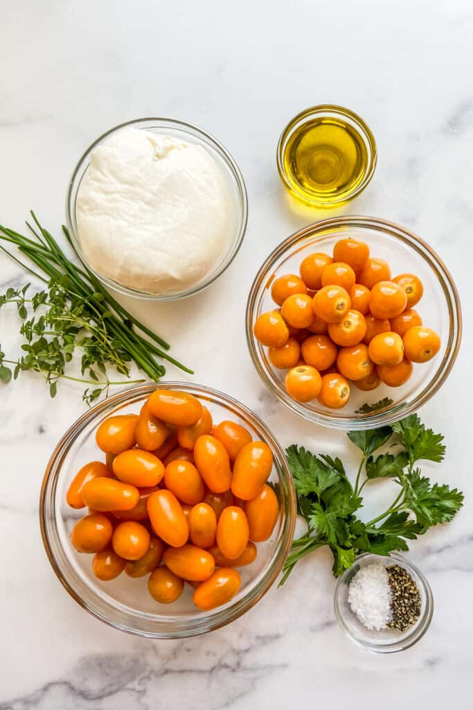 Bowls of ingredients for goldenberry tomato salad with buratta.