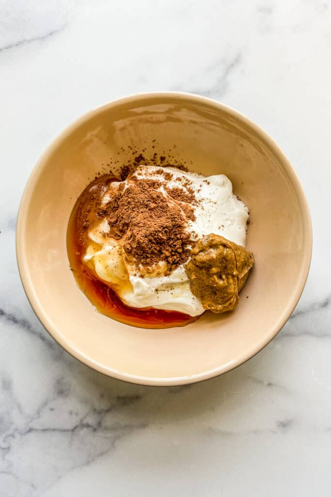 An overhead shot of a bowl with yogurt, honey, cocoa powder, and almond butter.
