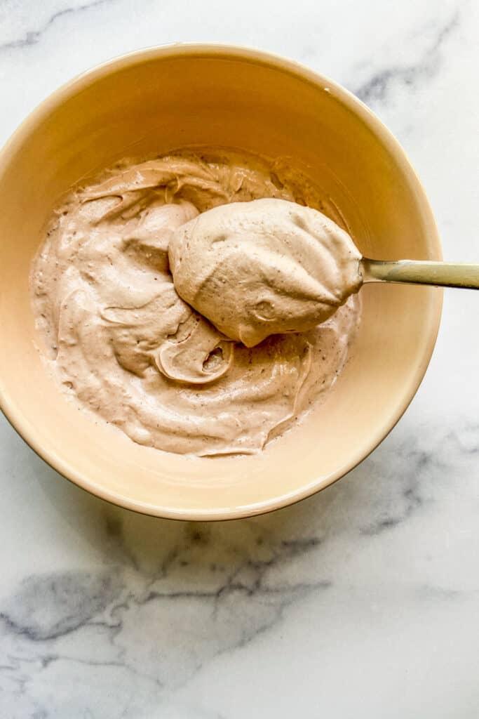 A bowl of Greek yogurt dessert dip with a silver spoon.