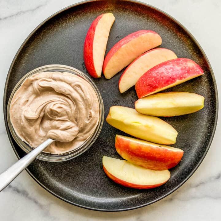 A small bowl of Greek yogurt dessert dip next to apple slices on a black plate.