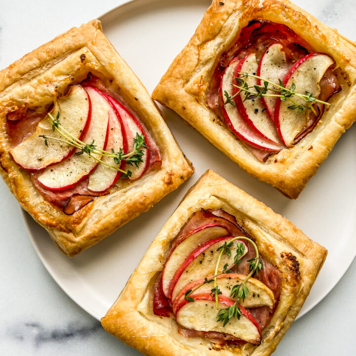 Three ham and cheese tarts on a white plate.