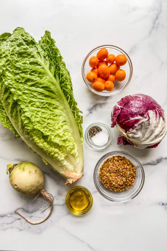 A head of lettuce, a bowl of kumquats, a head of raddichio, a bowl of dukkah, a bowl of olive oil, and a watermelon radish.