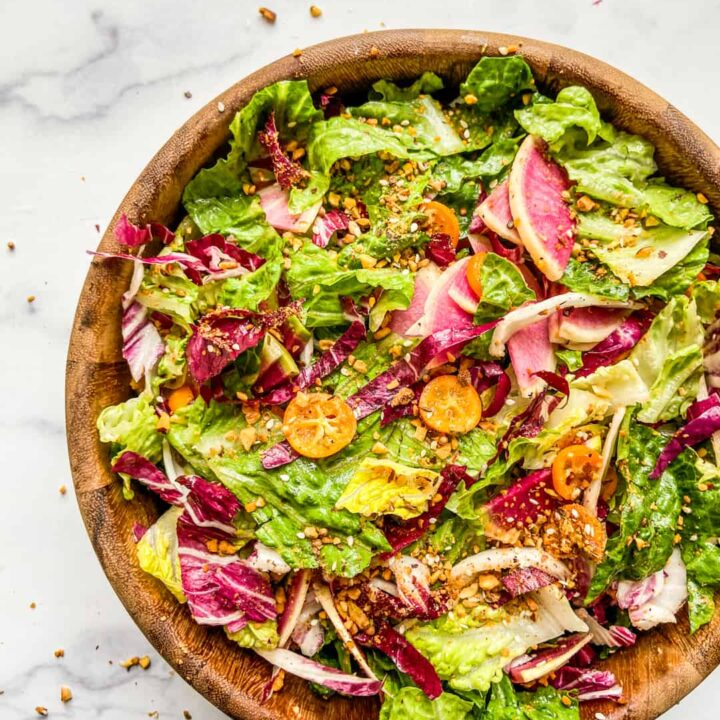 A large wooden salad bowl with a greens, radicchio, kumquats, and watermelon radishes.