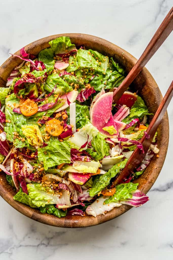 A large wooden salad bowl with a greens, radicchio, kumquats, watermelon radishes, and tongs.