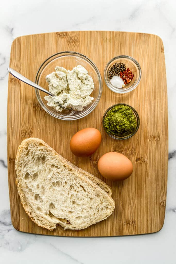 Two slices of sourdough bread, a bowl of goat cheese, two eggs, pesto, and seasonings on a wood cutting board.