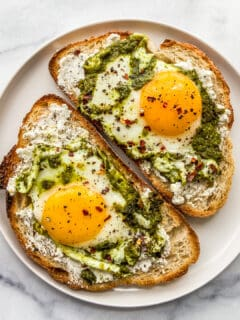 Two pieces of toast with pesto eggs on them.