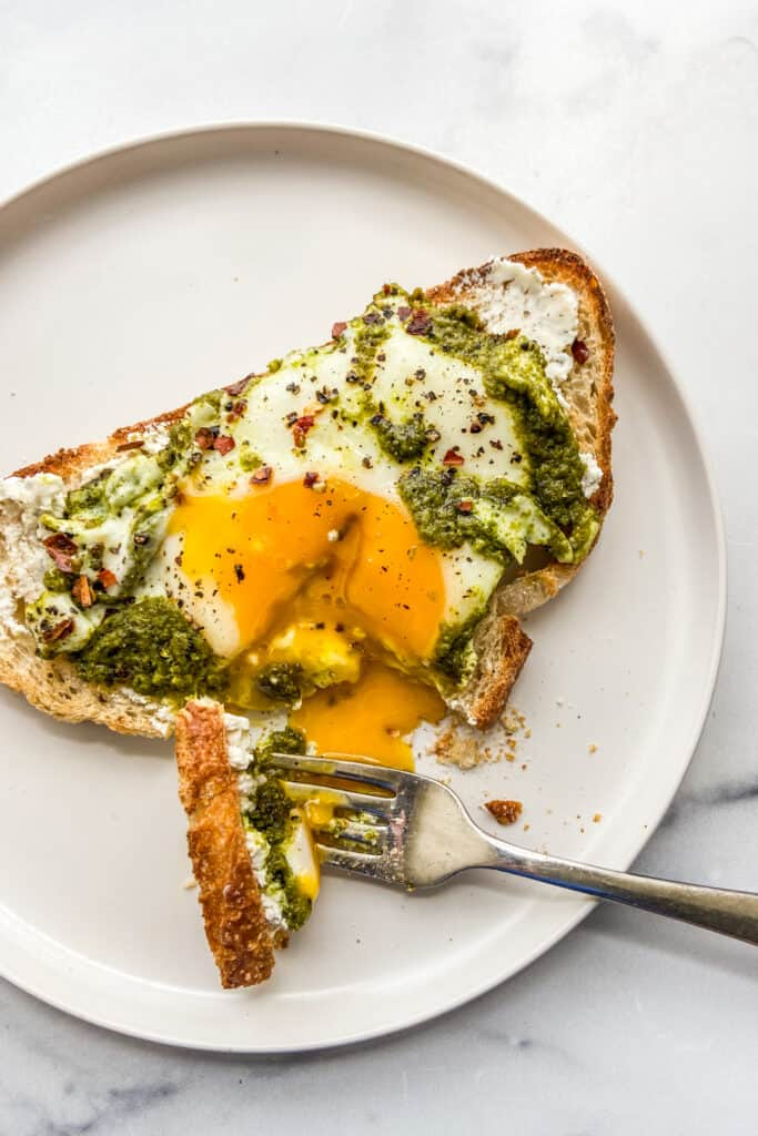 Pesto eggs on toast on a white plate with a fork.