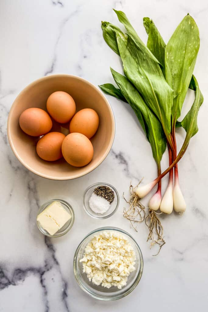 Eggs in a bowl, four ramps, a bowl of feta, butter, and a bowl of salt and pepper.