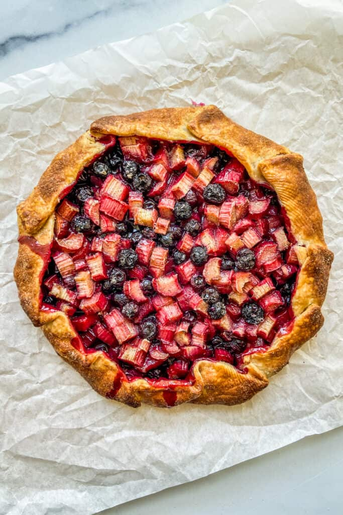 An overhead shot of a rhubarb blueberry galette right after it has come out of the oven.