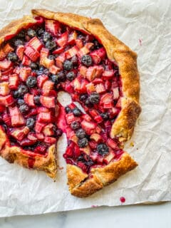 A rhubarb blueberry galette with a piece cut from it.