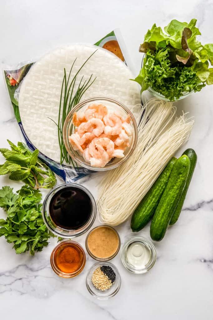 Ingredients for shrimp summer rolls on a marble background.
