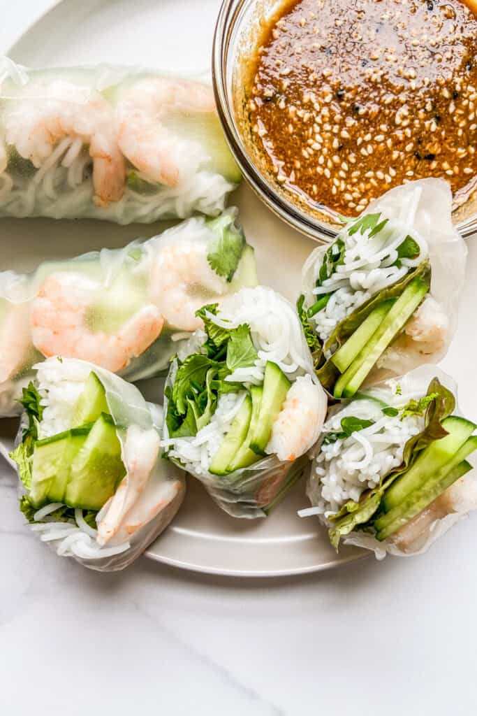 Shrimp summer rolls on a white plate next to a bowl of dipping sauce.