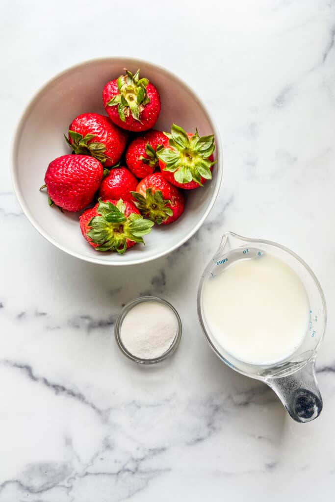 A bowl of strawberries, a measuring cup of milk, and a small bowl of sugar.