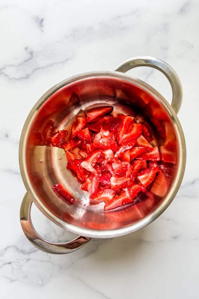 Macerated strawberries in a small pot.