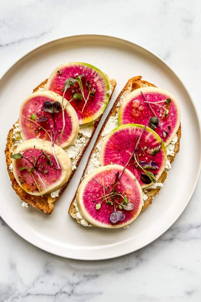 Two slices of toast with goat cheese and watermelon radish on a white plate.