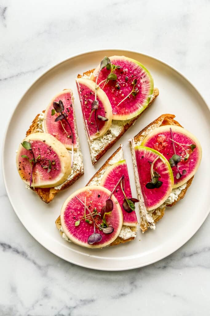 Watermelon radish toasts on a white plate.
