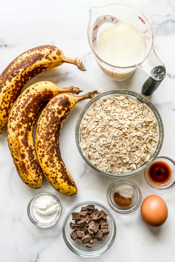 Three bananas, a measuring cup of milk, a bowl of oats, an egg, a bowl of baking powder, a bowl of chocolate chunks, a bowl of cinnamon and salt, and a bowl of vanilla.
