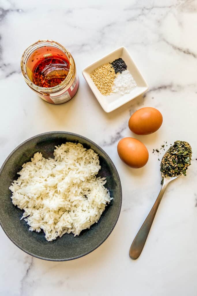 A jar of chili crunch oil, a bowl of sesame seeds, two eggs, a spoon of furikake, and a bowl of rice.